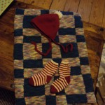 A patchwork blanket made from leftover sock yarn (WHY do people knit socks! Not even I love craft that much). Plus, Christmassy baby hat and socks. For sh*ts and giggles.